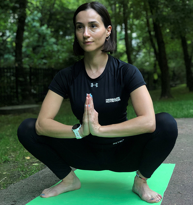 Emine Basarir performs the Garland Pose